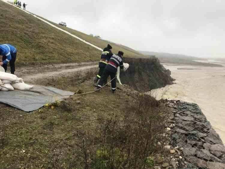 Zeci de pompieri lucrează la un dig sub amenințarea codului portocaliu de inundații pe râul Teleajen din Prahova
